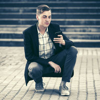 Young handsome business man using smart phone sitting in city street