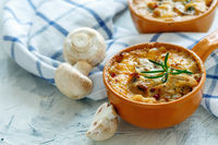 Roasted mushrooms, chicken and cheese gratin in pan.
