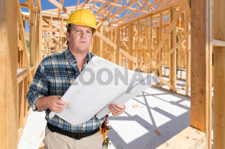 Male Contractor With House Plans Wearing Hard Hat Inside New House Construction Framing