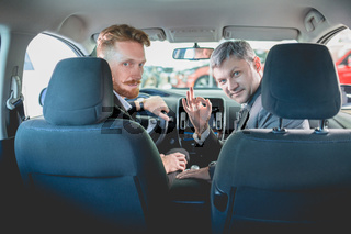 Vehicle dealer and buyer sitting on front seats in new car.