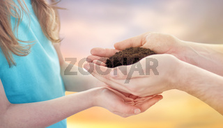 close up of father and daughter hands holding soil