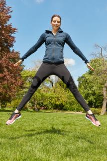 Sportliche Frau macht Luftsprung im Park