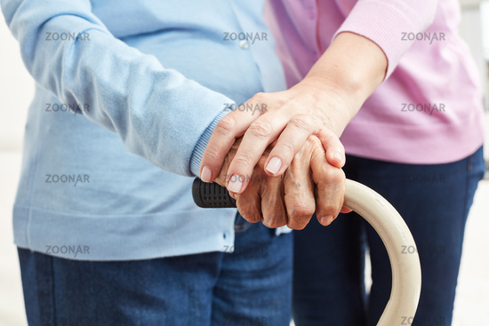 Hand einer jungen Frau berührt Hand einer Seniorin