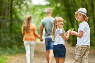 Kinder mit Eltern auf einer Wanderung im Wald