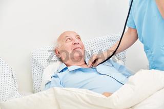 Krankenschwester mit Stethoskop hört Senior ab