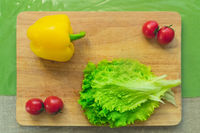 Fresh green lettuce leaves lie on a wooden cutting board next to the yellow bell pepper and red cherry tomatoes on a green table