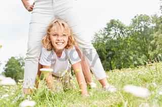 Junge spielt mit Mutter auf einer Wiese