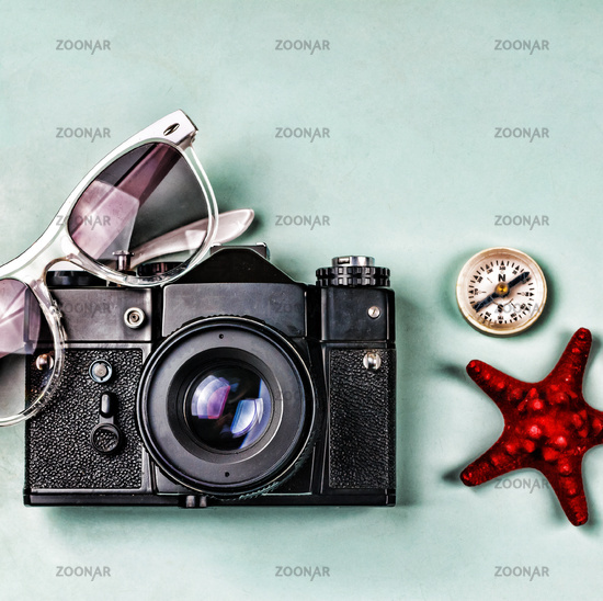 Ancient camera, compass and sea souvenirs on a blue background.