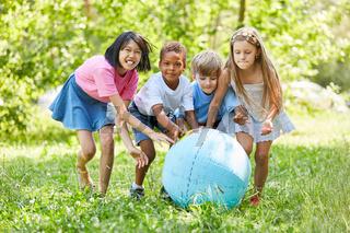 Gruppe Kinder spielt mit Weltkugel im Garten