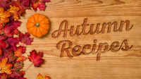 A wooden background with autumn foliage - Autumn Recipes