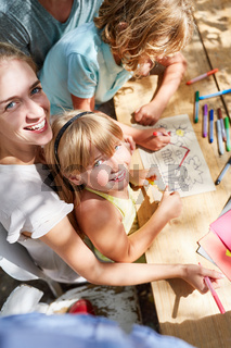 Mutter und Kinder malen mit Buntstiften