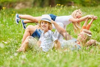 Junge mit Schwester und Familie im Gras