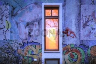 Beleuchtetes Fenster,  Hauswand  mit Graffiti