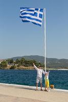 Tourists father and daughter near Greek flag on the Aegean coast of Sithonia peninsula