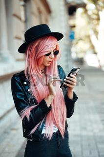 girl with pink hair with a smartphone