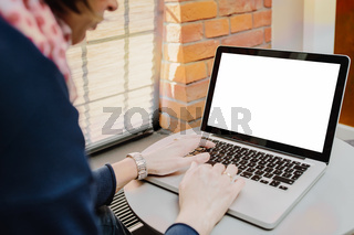 Woman using laptop with blank screen on table in office interior
