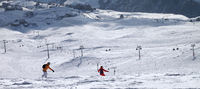 Two snowboarders downhill on freeride trace
