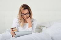 Attractive woman relaxing in bed online shopping