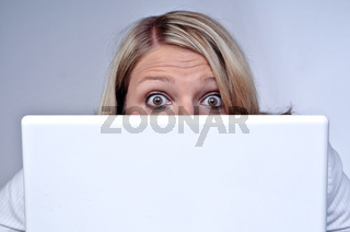 Woman Looking With Eyes Wide Open Behind Laptop