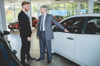Young man at auto showroom talking with vehicle dealer.