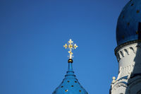 The gilded cross glows on the dome of the church Cathedral of the Holy Virgin on a blue sky background in the city of Gatchina, Leningrad region.