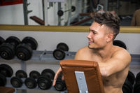 Shirtless young man resting in gym during workout