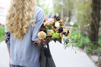 Young beautiful woman walking on the street with bag and bouquet of a flowers