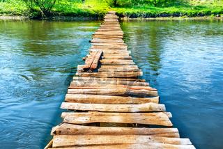 Old wooden bridge through the river