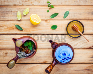 Assortment of dried herbal tea. Herbal tea pots with fresh herbs sage ,peppermint , honey, lime and lemon on rustic wooden background with flat lay.