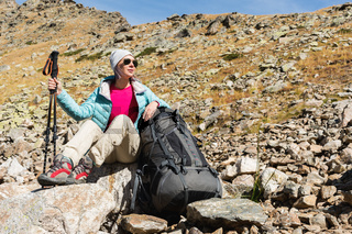 A tourist girl wearing sunglasses down jacket and hat with a backpack and mountain equipment with handles for tracking in her hands is sitting on high in the mountains