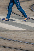 Woman in jeans crossing the road in town