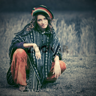 Young fashion hipster woman in rasta poncho sitting on the ground outdoor