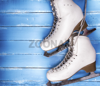 a pair of worn white leather skates for figure skating