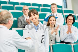 Handschlag zwischen junger Ärztin und Dozent