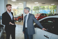 Handsome man at auto showroom talking with vehicle dealer.