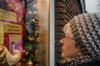 Eine einsame Seniorin betrachtet die weihnachtlich geschmückte Ankündigung einer Tanzschule.