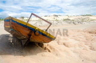 Back view of a broken canoe over the sand