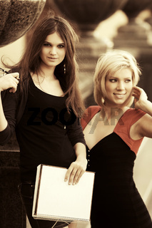 Two young fashion female students on campus