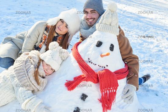 Glückliche Familie beim Schneemann bauen