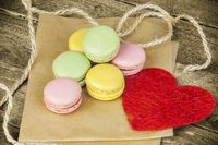 Macarons in various colors on paper near red paper heart