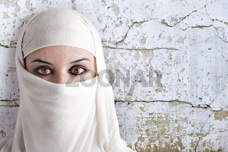 woman dressed in Arab costume, rusty wall in the background