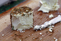Fresh goat cheese with knife on wooden board