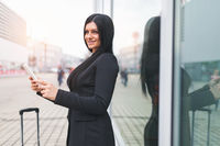 Young beautiful business woman with tablet and suitcase in an urban setting