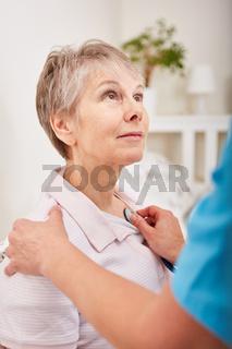 Krankenschwester horcht Seniorin ab