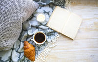 Cup of coffee, croisan and book on the floor