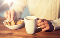 close up of woman with cookies and hot chocolate