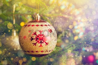Christmas-tree decoration bauble on decorated Christmas tree bac