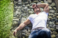 Confident attractive man on stone wall