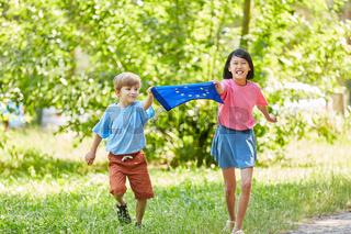 Kinder laufen mit Europa Fahne im Park