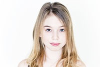 Teenager girl with blond long hair and big eyes on white wall